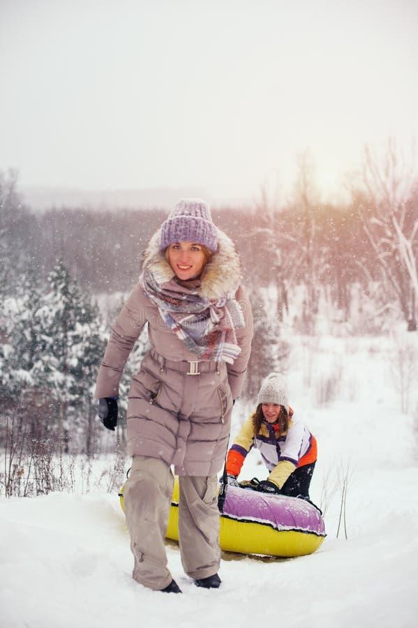 Twee vrouwelijke vrienden die pret op sneeuwheuvel hebben stock fotografie