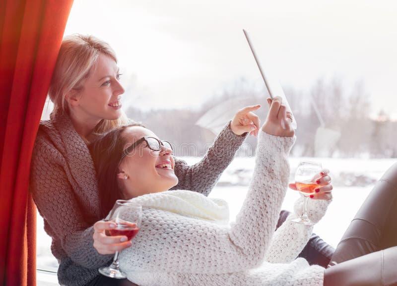 Twee vrouwelijke vrienden die tabletcomputer bekijken stock foto