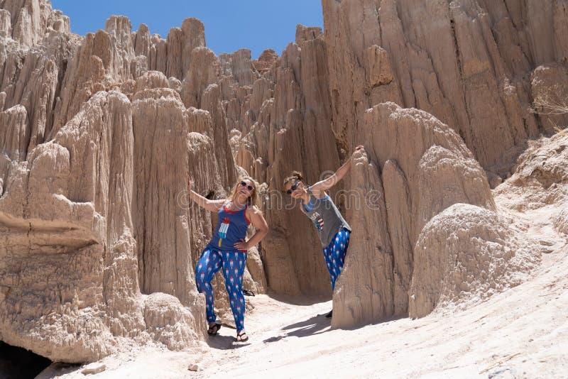 Twee vrouwelijke vrienden gluren uit achter rotsen bij het Park van de Staat van de Kathedraalkloof stock afbeelding