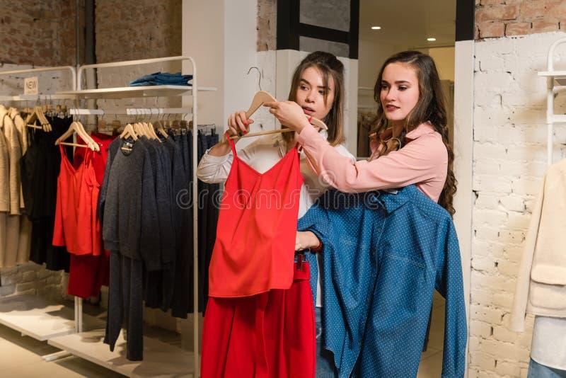 Twee vrouwelijke vrienden in kleren bij opslag stock foto's