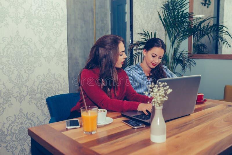 Twee vrouwelijke vrienden, studenten samen gebruikend laptop en drinkend koffie royalty-vrije stock foto