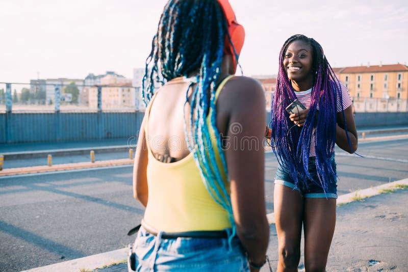 Twee vrouwelijke zusters in de buitenlucht die muziek dansen stock foto