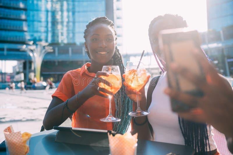 Twee vrouwelijke zusters in de buitenlucht die selfie innemen stock fotografie