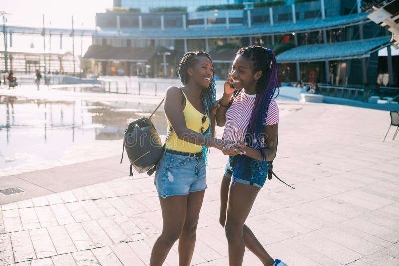 Twee vrouwelijke zusters in de buitenlucht met smartphone die plezier maakt royalty-vrije stock fotografie