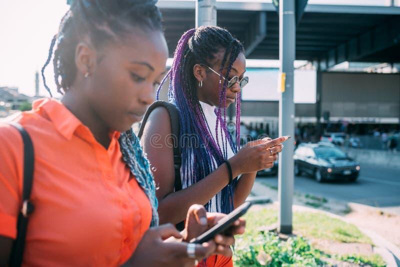Twee vrouwelijke zusters die buiten lopen met smartphone royalty-vrije stock foto