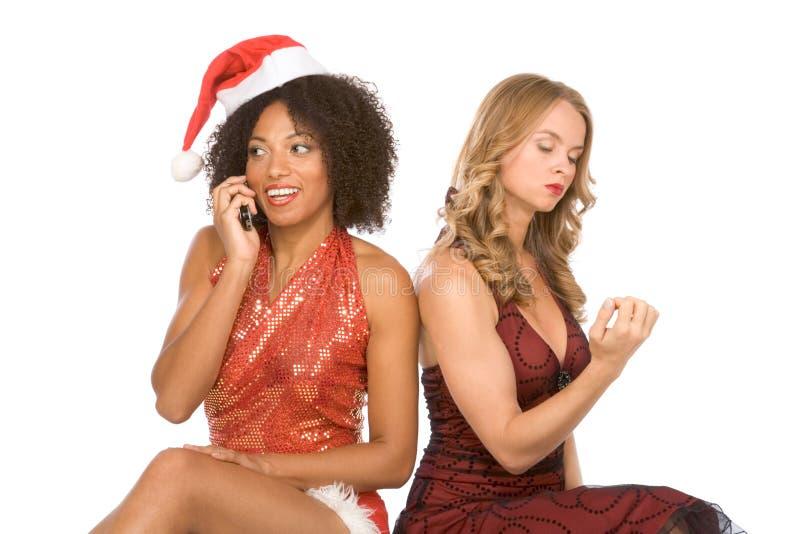 Twee vrouwen één die van Kerstmis op celtelefoon spreken royalty-vrije stock afbeelding