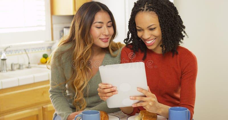 Twee vrouwen beste vrienden die ontbijt eten en tabletcomputer met behulp van stock fotografie