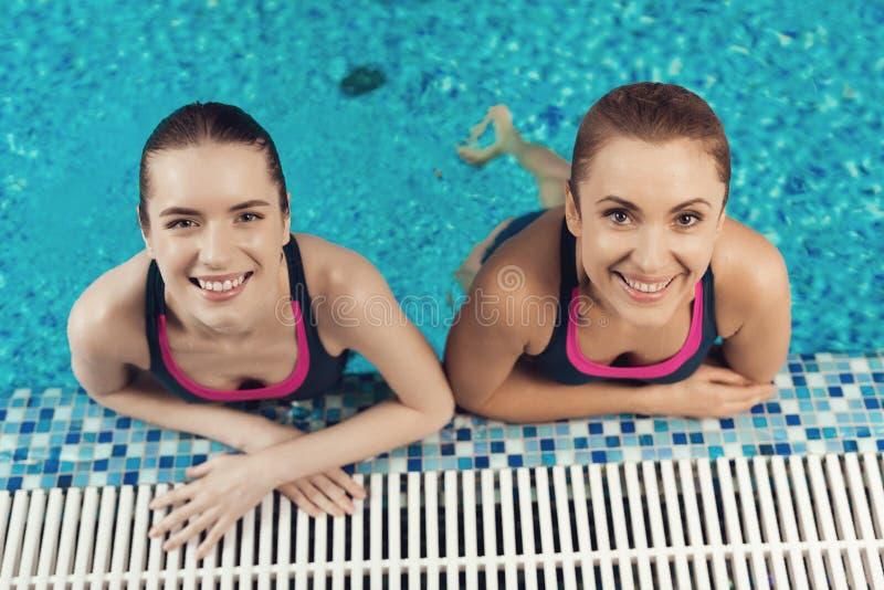 Twee vrouwen bij de grens van pool bij de gymnastiek Het mamma en de dochter kijken gelukkig, modieus en geschikt royalty-vrije stock foto