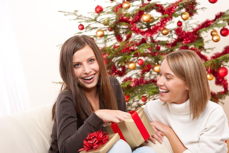 Twee vrouwen die aanwezige Kerstmis uitpakken royalty-vrije stock foto's