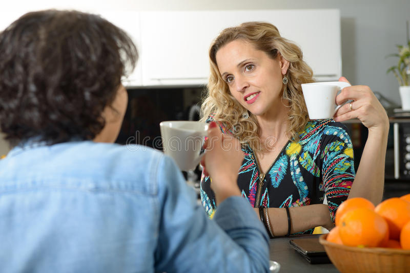 Twee vrouwen die bij lijst in keuken en het drinken koffie zitten royalty-vrije stock foto