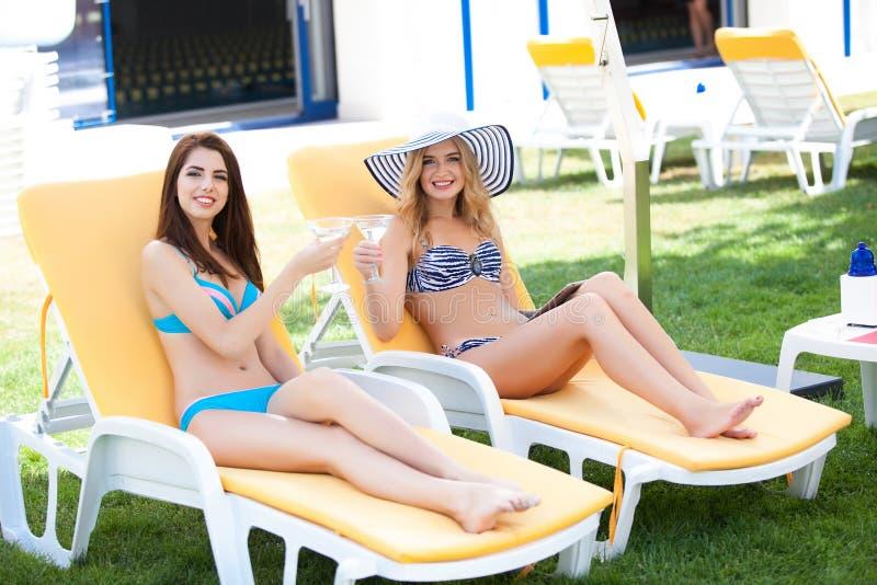 Twee vrouwen die de zomer van vakantie met cocktails genieten door pool stock fotografie