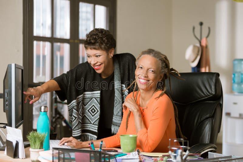 Twee Vrouwen die in een Creatief Bureau samenwerken stock foto's