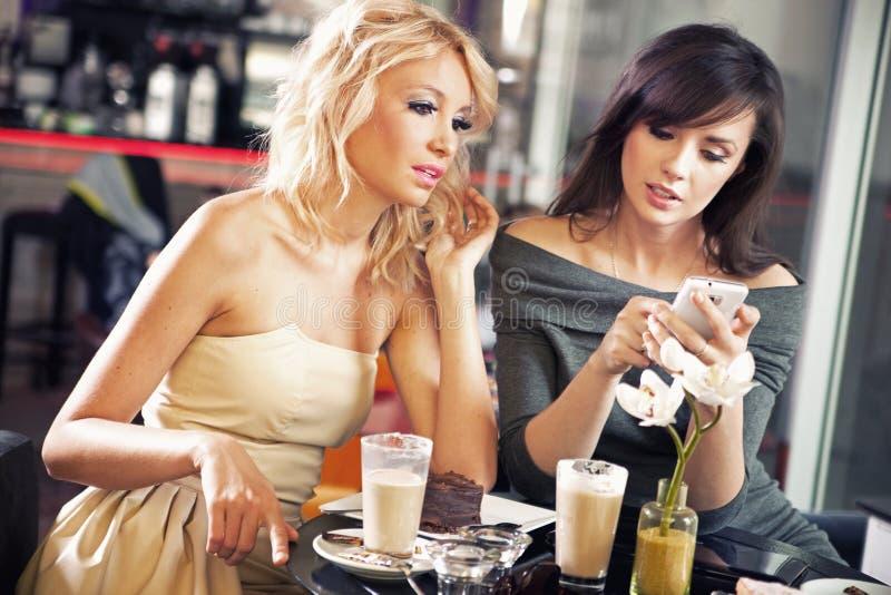 Twee vrouwen die een smartphone gebruiken royalty-vrije stock foto