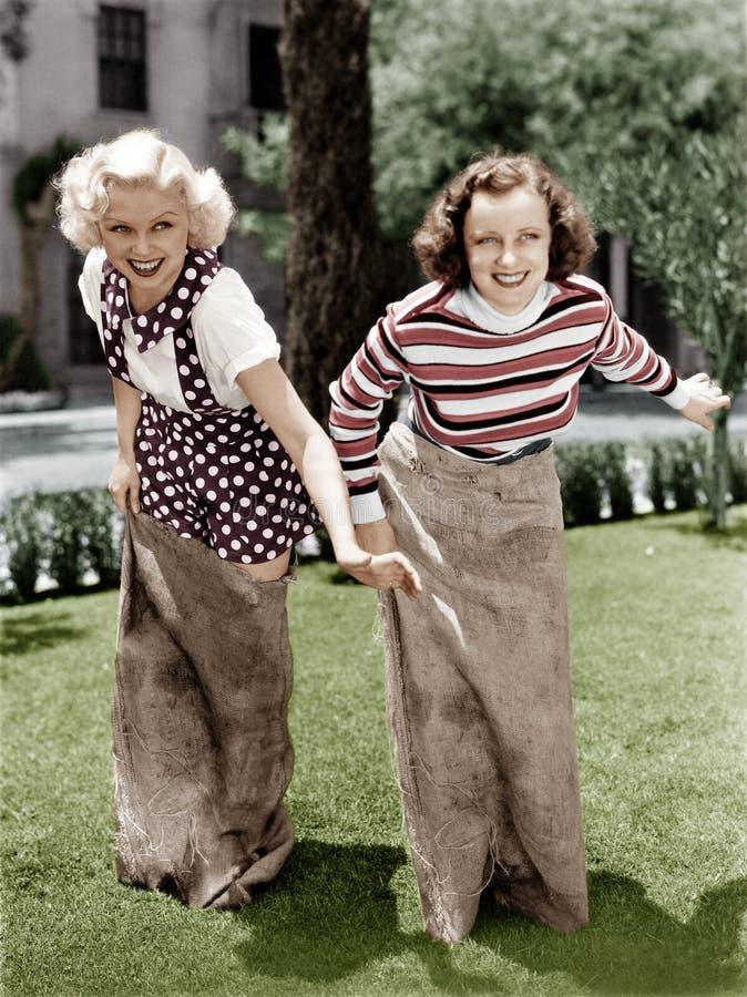 Twee vrouwen die een spel van aardappelzak het rennen spelen (Alle afgeschilderde personen leven niet langer en geen landgoed bes royalty-vrije stock fotografie