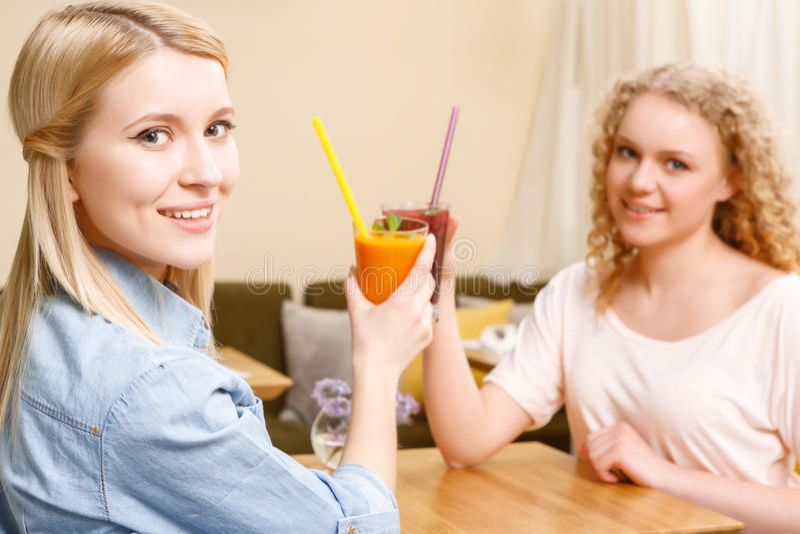 Twee vrouwen die glazen met cocktails in koffie clinking royalty-vrije stock foto's
