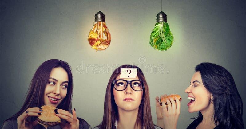 Twee vrouwen die hamburgers eten die nadenkend meisje met vraagteken bekijken stock foto