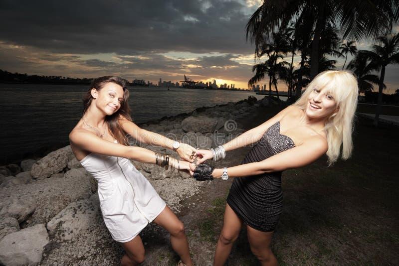 Twee vrouwen die handen en het slingeren houden stock afbeeldingen