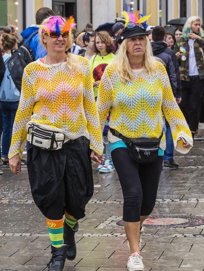 Twee vrouwen die handen houden en gele sweaters dragen die die de Gay Pride-parade bijwonen ook als Christopher Street Day, Münch stock fotografie
