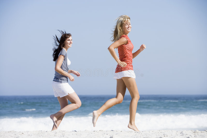 Twee vrouwen die langs strand lopen stock foto's