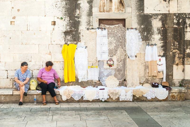 Twee vrouwen die met de hand gemaakt borduurwerk in Zadar, Kroatië aanbieden stock foto