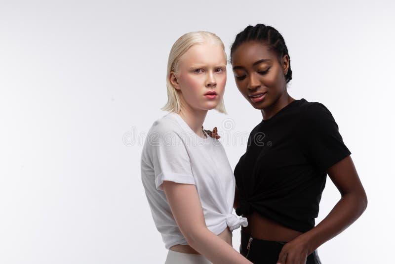 Twee vrouwen die met verschillende kleur korte duidelijke t-shirts dragen stock foto's