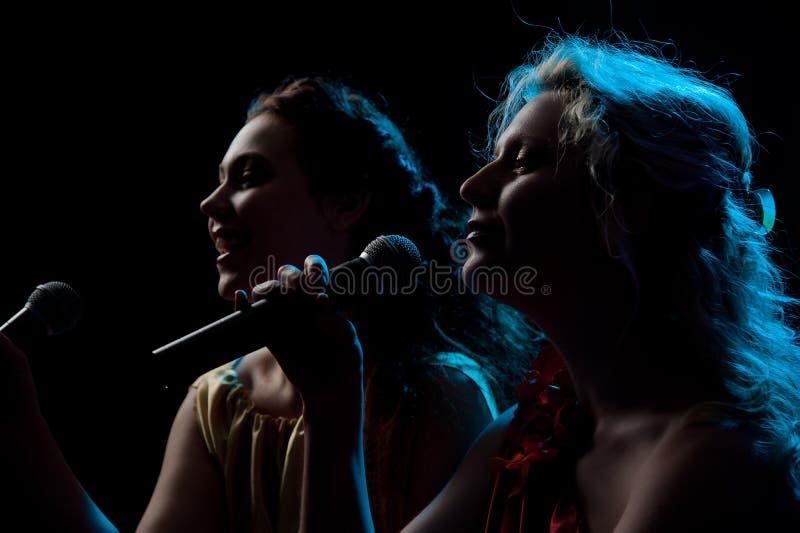 Twee vrouwen die in microfoon zingen royalty-vrije stock afbeeldingen