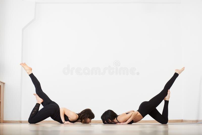 Twee vrouwen die neer met gezicht aan vloer in witte studio buigen Het praktizeren de yoga van partneracro stelt en asanas voor b stock foto
