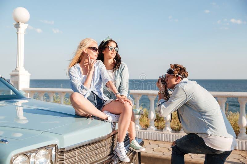 Twee vrouwen die op auto zitten en aan man fotograaf stellen royalty-vrije stock fotografie