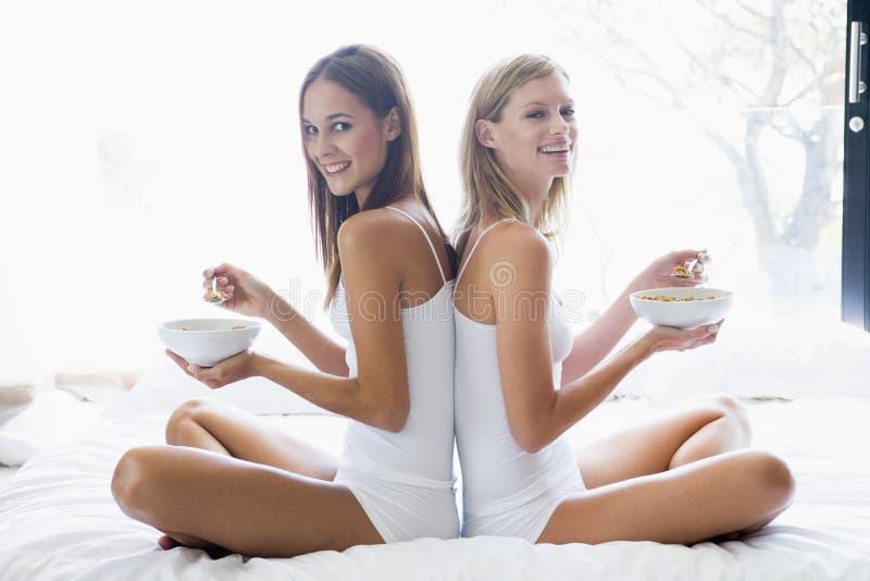 Twee vrouwen die op bed zitten dat graangewas eet stock afbeelding