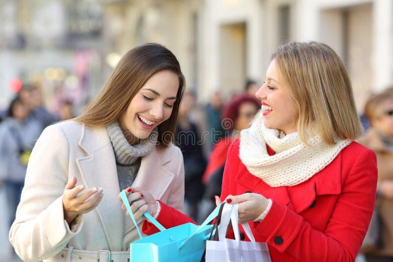Twee vrouwen die op de straat in de winter shooping stock foto