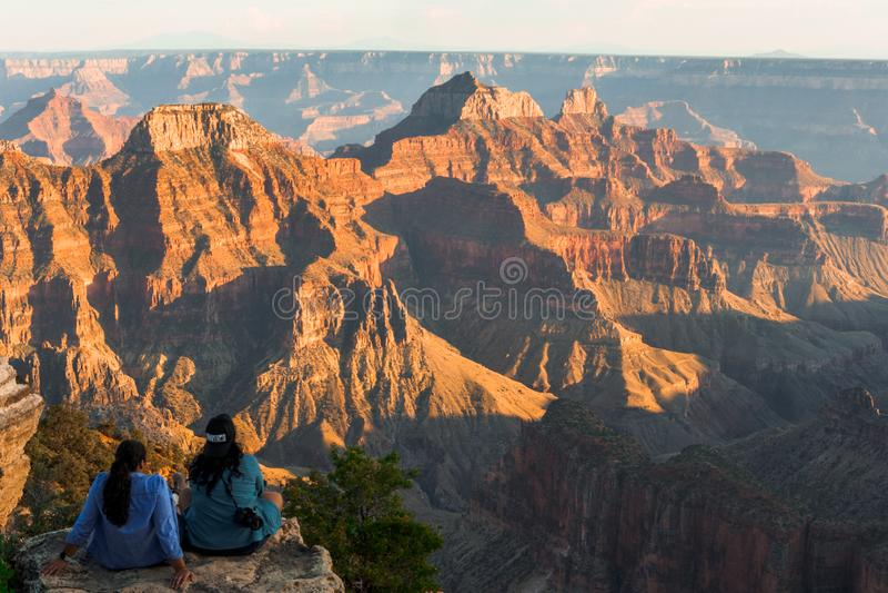 Twee vrouwen die op een rots zitten die van de mening van de het Noordenrand genieten in Grote Canyo royalty-vrije stock fotografie