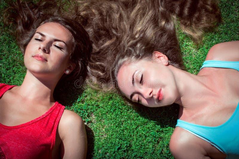 Twee vrouwen die op groen gras ontspannen stock afbeeldingen