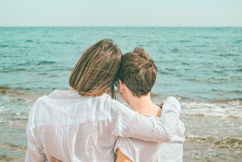 Twee vrouwen die op het strand koesteren royalty-vrije stock foto's