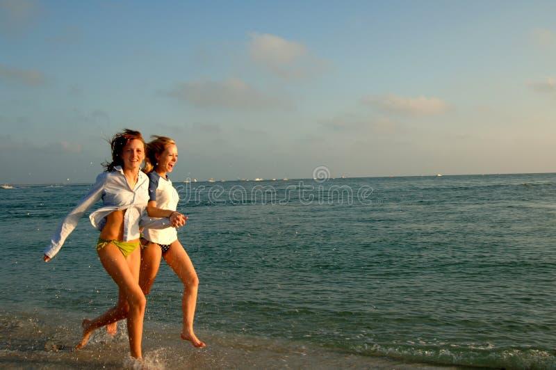 Twee vrouwen die op strand lopen stock afbeelding
