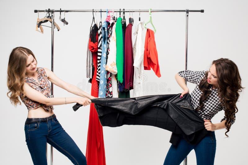 Twee vrouwen die over het winkelen zak met woedende uitdrukkingen vechten stock foto