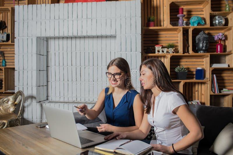 Twee vrouwen die overleg hebben, die laptop computer met behulp van royalty-vrije stock fotografie