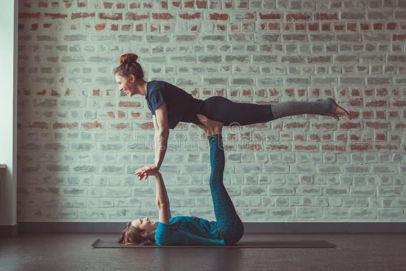 Twee vrouwen die partneryoga in yogastudio doen tegenover bakstenen muur stock afbeelding