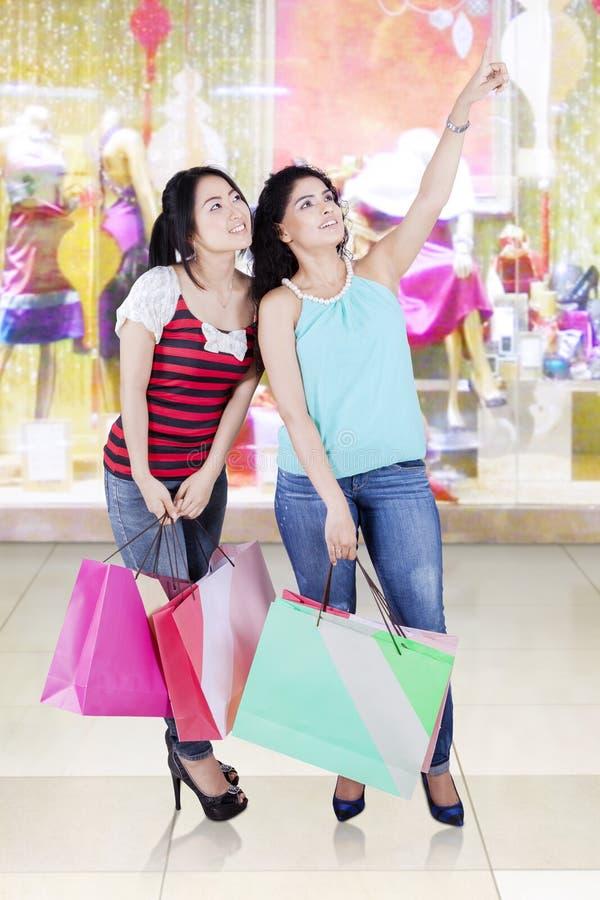 Twee vrouwen die samen in wandelgalerij winkelen royalty-vrije stock foto's