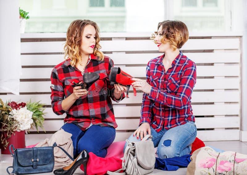 Twee vrouwen die schoenen van haar garderobe kiezen het concept manier stock fotografie