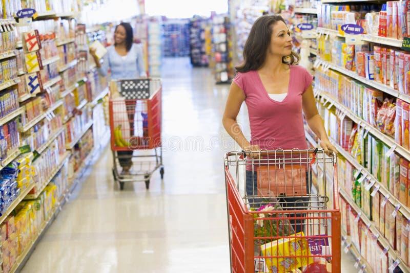Twee vrouwen die in supermarkt winkelen royalty-vrije stock fotografie