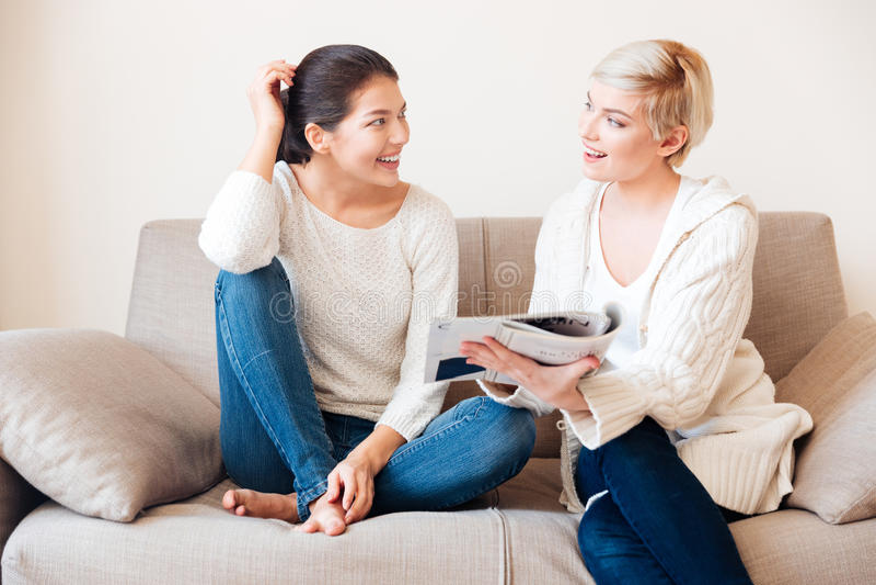 Twee vrouwen die tijdschrift op de bank lezen stock foto
