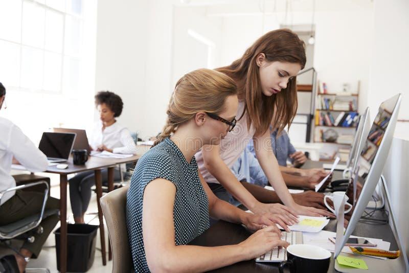 Twee vrouwen die van een document in open planbureau werken stock foto's