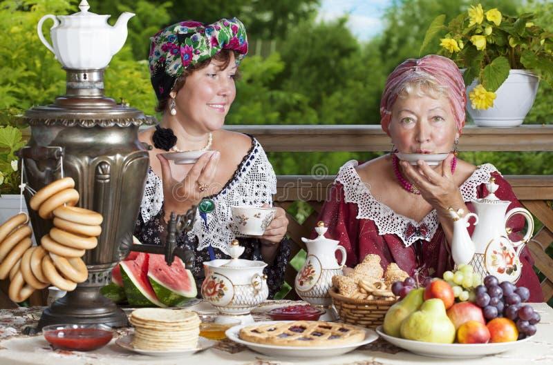 Twee vrouwen die van een kop thee genieten stock afbeeldingen