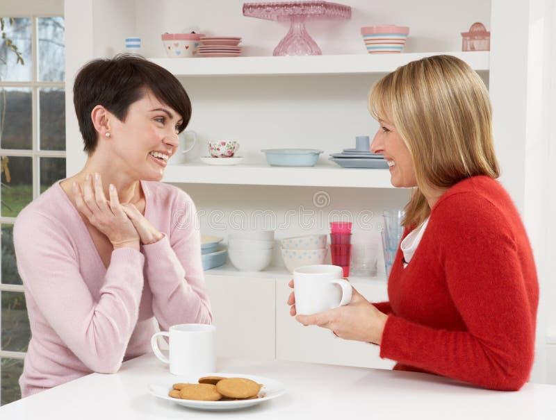 Twee Vrouwen die van Hete Drank in Keuken genieten royalty-vrije stock foto