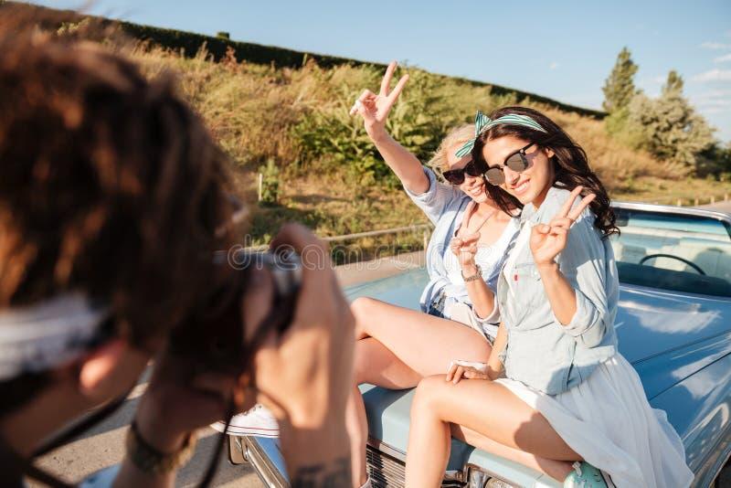 Twee vrouwen die vredesteken tonen en aan man fotograaf stellen royalty-vrije stock foto's