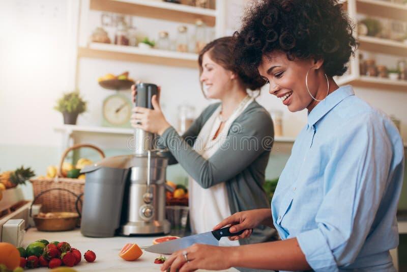 Twee vrouwen die vruchtensap voorbereiden bij koffie stock foto's