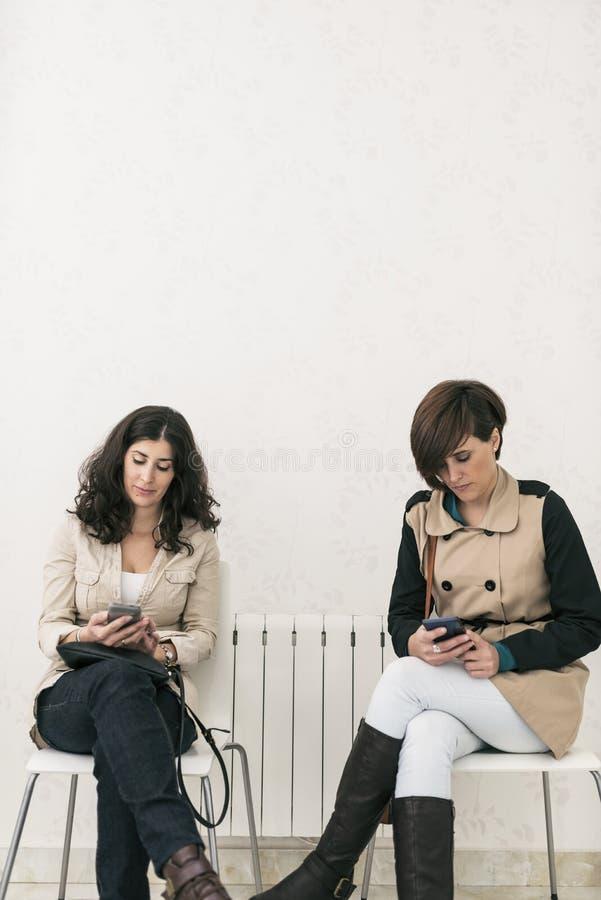 Twee vrouwen die in wachtkamer ernstige smartphone kijken royalty-vrije stock afbeelding