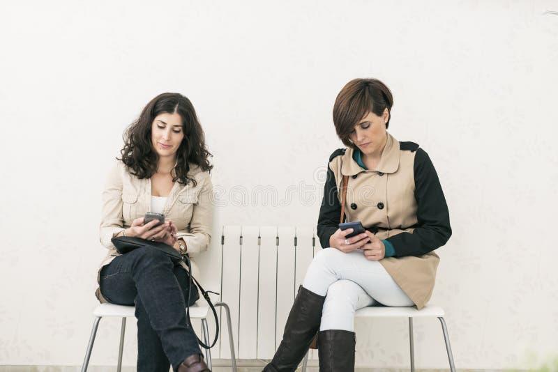 Twee vrouwen die in wachtkamer ernstige smartphone kijken royalty-vrije stock afbeeldingen