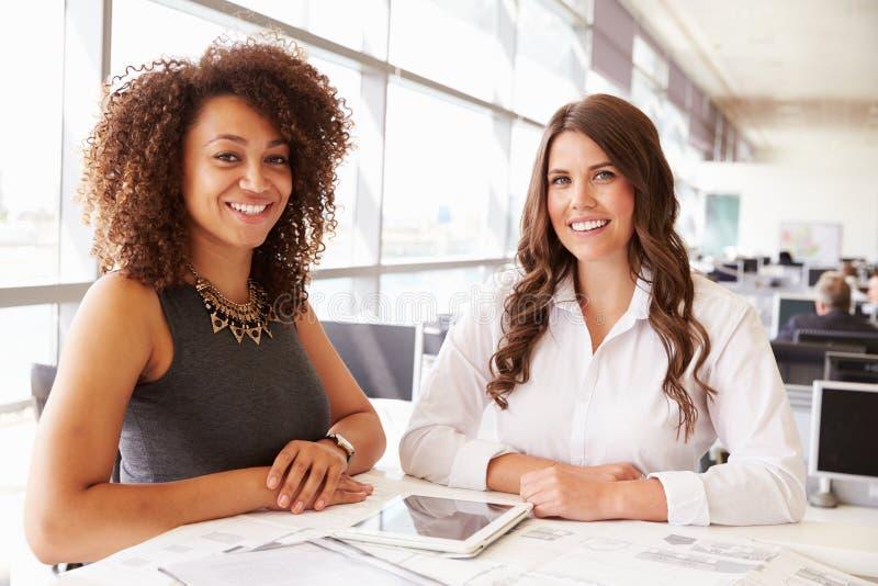 Twee vrouwen die werken bij een architect? s bureau die aan camera kijken royalty-vrije stock afbeeldingen