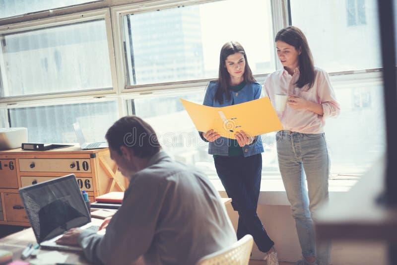 Twee vrouwen die werkplan in bureau bespreken Mens die aan laptop werkt Coworking en open plekbureau stock afbeeldingen